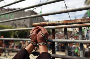 A Hamas supporter acting as a Palestinian prisoner stands in a mock cage during a rally in Jabalya, in the northern Gaza Strip, April 13, 2012, calling for the release of Palestinian prisoners from Israeli jails. REUTERS/Mohammed Salem (GAZA - Tags: POLITICS CIVIL UNREST)