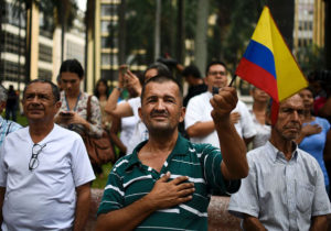 People sing the national anthem in Cali, Colombia, on June 23, 2016 celebrating the peace agreement between the Colombian governenment and the FARC leftist guerrilla to be signed today in Havana.  Colombia's government and the FARC guerrilla force signed a definitive ceasefire Thursday, taking one of the last crucial steps toward ending Latin America's longest civil war. / AFP / LUIS ROBAYO        (Photo credit should read LUIS ROBAYO/AFP/Getty Images)